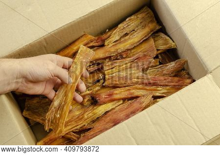 A Man's Hand Pulls Dried Beef Tendon Out Of A Cardboard Box. Natural Healthy Chewable Treats For Pet