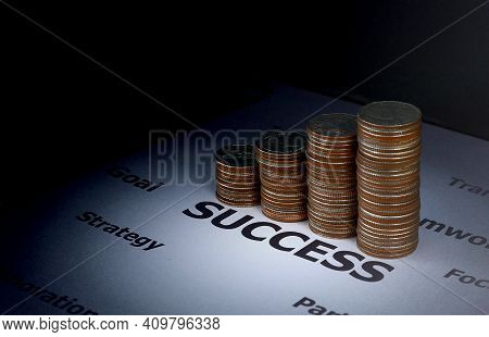Finance And Investment Concept - Stack Of Coins On Success Word Which Surround With Other Factor To