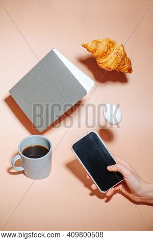Croissant, Egg And Notebook Hovering In Air. Hand Taking Picture On A Phone.