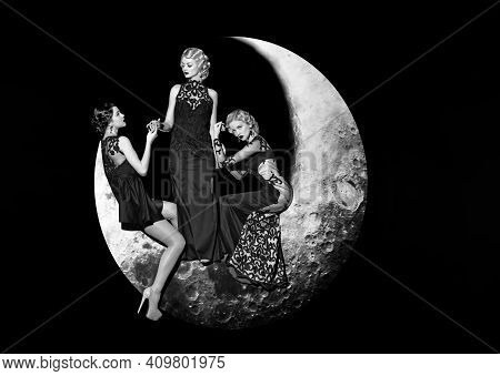 Fashion Dress. Group Of Beautiful Young Women Posing On Crescent Moon In Long Evening Elegant Dress