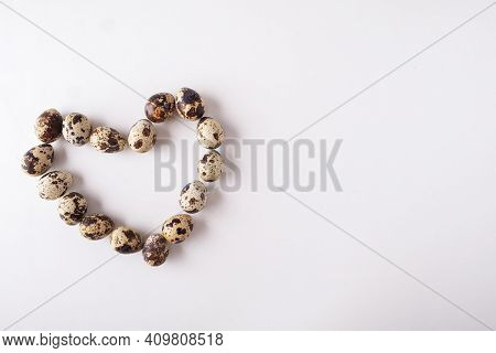 Quail Eggs Are Isolated On A White Background. Shape Of Heart From The Quail Of Eggs With Copy Space