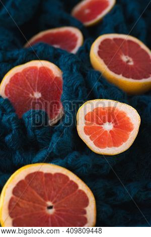 Sliced Pieces Of Grapefruit Lie On A Green Knitted Blanket. Grapefruit Slices On A Green Background