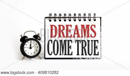 Dreams Come True Concept Notepad Writing On White Background With Alarm Clock