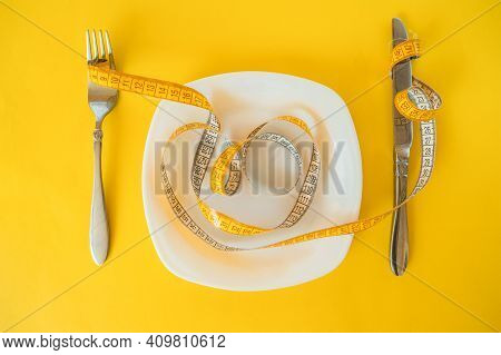 Measuring Tape On Fork And Plate And Knife On A Yellow Background. Body Weight Loss Concept.