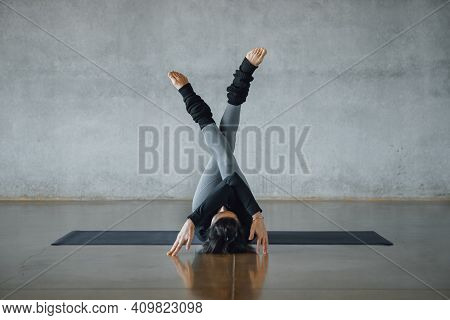 Fit Young Woman Coach Practices Individual Hatha Yoga On A Black Mat In A White Background, Pilates