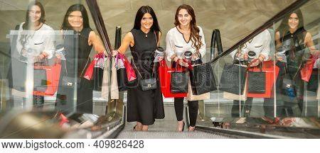 Two Beautiful Young Caucasian Women With Shopping Bags Moving Up On Escalator Looking At The Camera