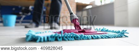 Man With Mop Washes Floor In Office. Cleaning Company Services Concept