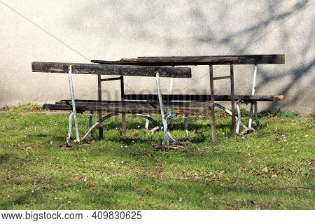 Dilapidated Old Makeshift Homemade Table In Middle Of Two Wooden Public Park Benches With Rusted Bro