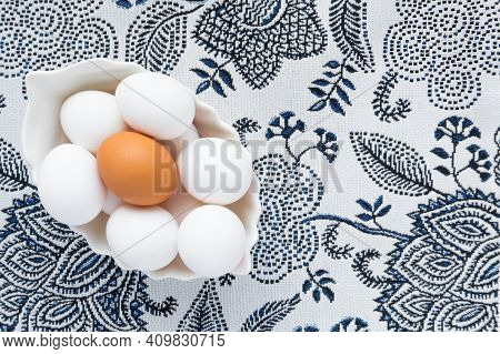 Many White Eggs And One Brown Egg In A White Dish Against The Background Of A Patterned Tablecloth.