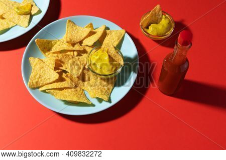 Nachos Chips With Cheese Sauce On Blue Plate, Soda Bottle And Hot Sauce On Red Background. Food Phot