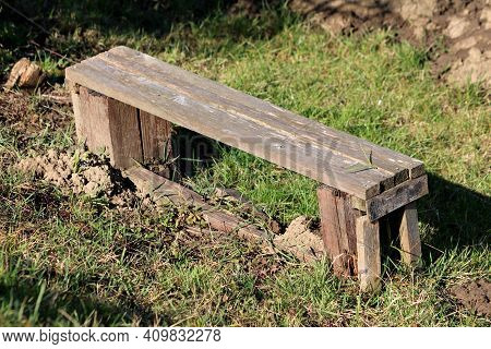 Improvised Homemade Cracked Dilapidated Wooden Boards Small Bench Left In Urban Home Garden Surround