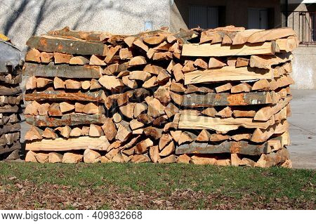 New Fresh Neatly Stacked Firewood Left In Family House Driveway Next To Old Pile Of Firewood Surroun