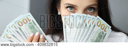 Woman Holds One Hundred Dollar Bills At Face Level And Looks At Camera. Earnings For Women Concept