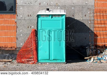 Used Light Green Portable Ecological Toilet Left On Construction Site Next To Unfinished Building Wa