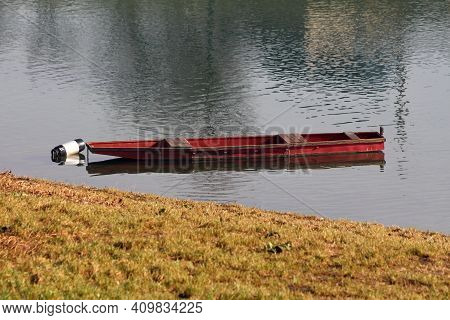 Used Old Elongated Red River Boat Made Of Dilapidated Wooden Boards Tied To Black And White Buoy Nex