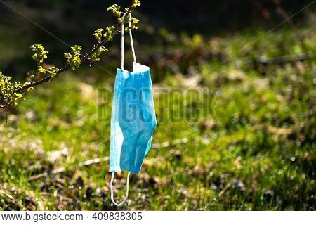 End Of The Pandemic. A Medical Mask Is Hanging. A Disposable Medical Mask Hanging On A Twig.