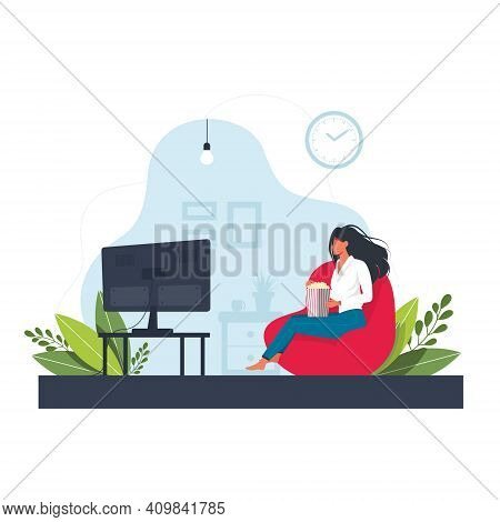 A Young Woman Is Sitting On The Pouf, Watching Tv And Eating Popcorn. The Concept Of Daily Life, Eve