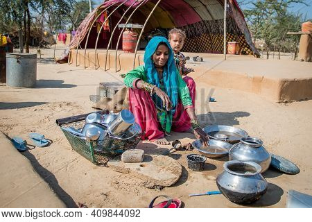 Rajasthan. India. 07-02-2018. Mother Is Cleaning Dishes While Taking Care Of Her Baby In A Village I