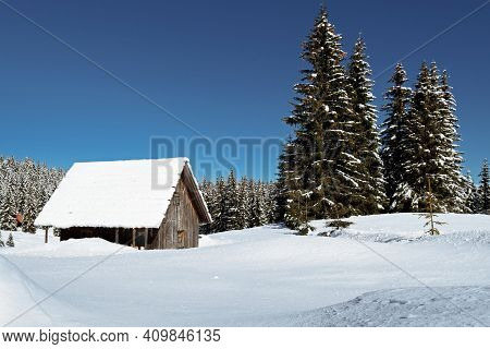 Wooden Alpine Cabin In Beautiful Idyllic Winter Landscape. Seasons, Weather, Holidays And Travel Con