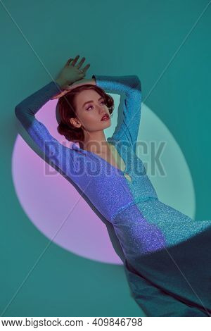 Stunning young woman in a long elegant dress and with hair and makeup in the style of the 20s posing in the circle of light. Light and shade.