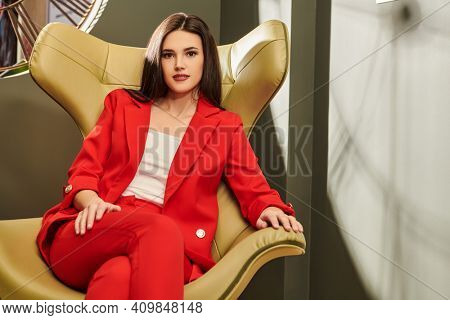 Portrait of a beautiful business lady sitting in a chair in a modern office. Business, elegant business woman. Interior, furniture.