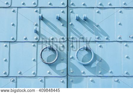 Steel door with rings door handles and metal rivets. Steel door of light blue color, medieval steel gates, steel backgorund, steel texture, steel gates