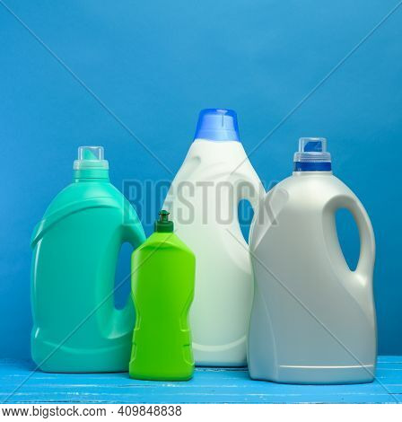 Plastic Bottles With Detergents On Blue Background, Close Up
