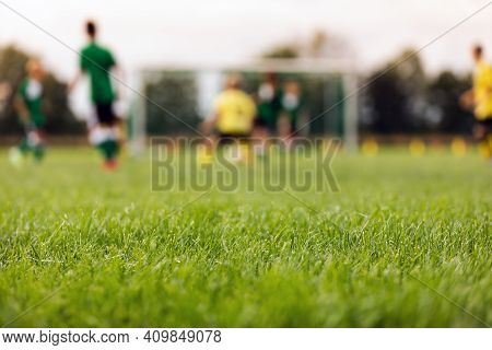 Soccer Stadium Field. Training Field In The Blurred Background.. Grass Football Pitch. Kids Playing