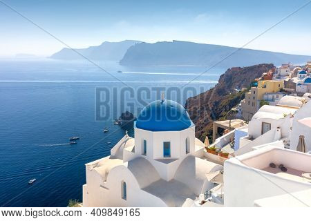 Famous view of Oia town cityscape at Santorini island in Greece. Traditional blue dome and white houses. Greece, Aegean sea. Famous European destination