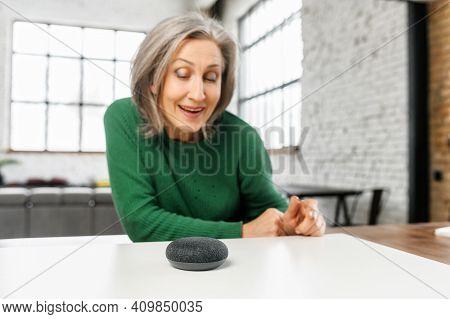 Senior Elderly Modern Woman Is Using Voice Commands For Wireless Smart Speaker Control. Smart Home A
