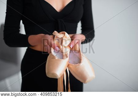 Gold-colored Pointe Shoes In The Hands Of A Professional Ballerina.