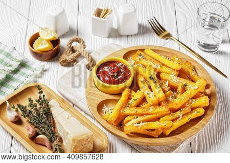 Garlic Parmesan Polenta Fries With Parmesan Cheese, Thyme And Spices In A Bamboo Dish With Tomato Sa