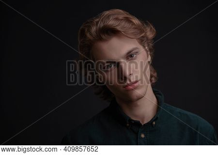 Portrait of a handsome young man with wavy blond hair looking at the camera. Black background with copy space. Men's beauty. Copy space.