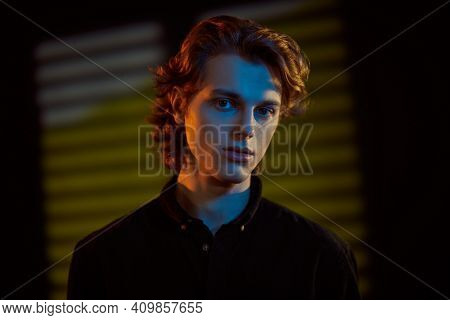 Portrait of a handsome young man with wavy blond hair on a dark background with mixed color light and shadows. Men's beauty.