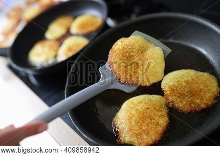 Chef Turning Potato Pancakes With Spatula Closeup. Belarusian National Cuisine Concept