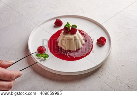 Womans Hand Puts Tweezers Leaf Mint To Panna Cotta With Syrup, Raspberries And Mint, High Key, Close