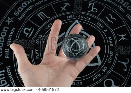 Hand Holding A Glass Ball With Horoscope Reflections. Black Background With Horoscope Signs.