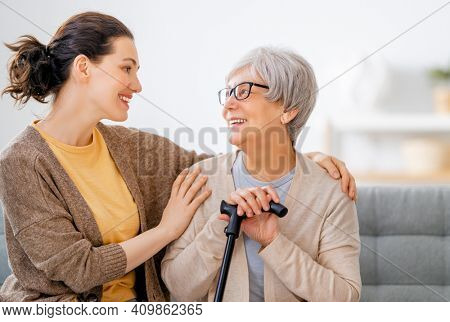 Happy patient and caregiver spending time together. Senior woman holding cane.