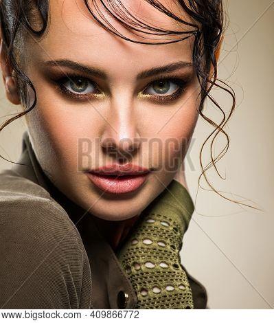 Closeup portrait of a beautiful young fashion woman with glamour makeup posing at studio. Smokey eye make-up. Beautiful  woman Face with a bang. Model looking at camera. Sexy woman looks at camera.
