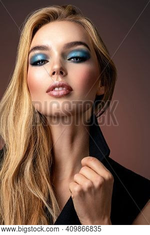Photo of young stylish  woman in black clothes with  blue make-up. Portrait of sexy blonde woman with a beautiful face. Fashion model with long hair, studio shot. Fashion concept.