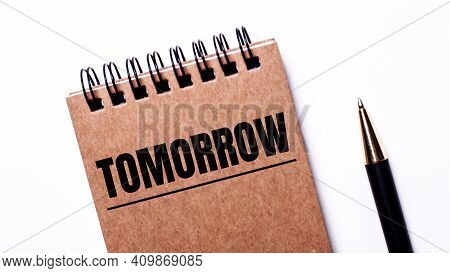 On A Light Background, A Black Pen And A Brown Notebook On Black Springs With The Inscription Tomorr