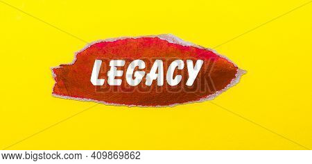 On A Yellow Background, A Sheet Of Red Paper With The Word Legacy
