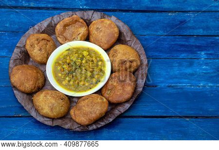 Khasta Kachori Or Kachodi With Curried Yellow Peas Or Ghugni Curry In A Leaf Plate Isolated  Blue Wo