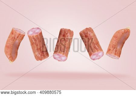 Pieces Of Bavarian Hunting Sausage In The Air. Chopped Hunting Sausage. Falling Sausage Or Meat