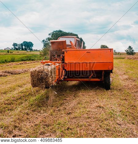 The Tractor Collects Dry Hay In The Field, The Hay Presses The Bale Press, Work In The Field.