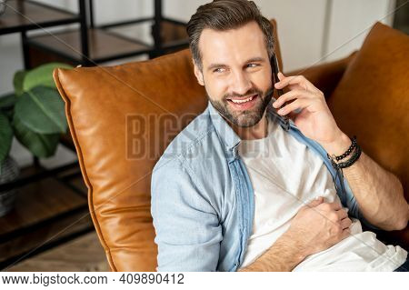 Close-up Of Young Bearded Hipster Man Lying Down On A Comfy Couch Answered The Phone Call And Having