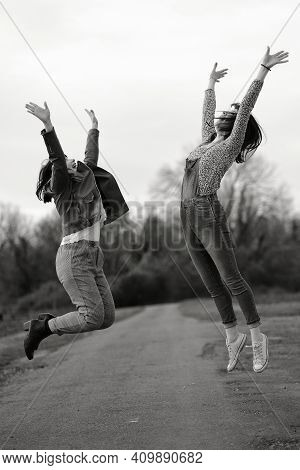 Two Young Women Jumping High Of Joy And Happiness