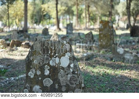 Old Muslim Turkish Cemetery. Old Headstone At Cemetery. Blurred Graveyard Background.