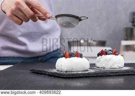 Cakes Anna Pavlova. Pastry Chef Sprinkles Icing Sugar On Berry Cakes