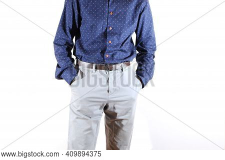 Businessman In Shirt And Trousers, Hands In Pockets. Male Model In A Blue Shirt And Light-colored Tr
